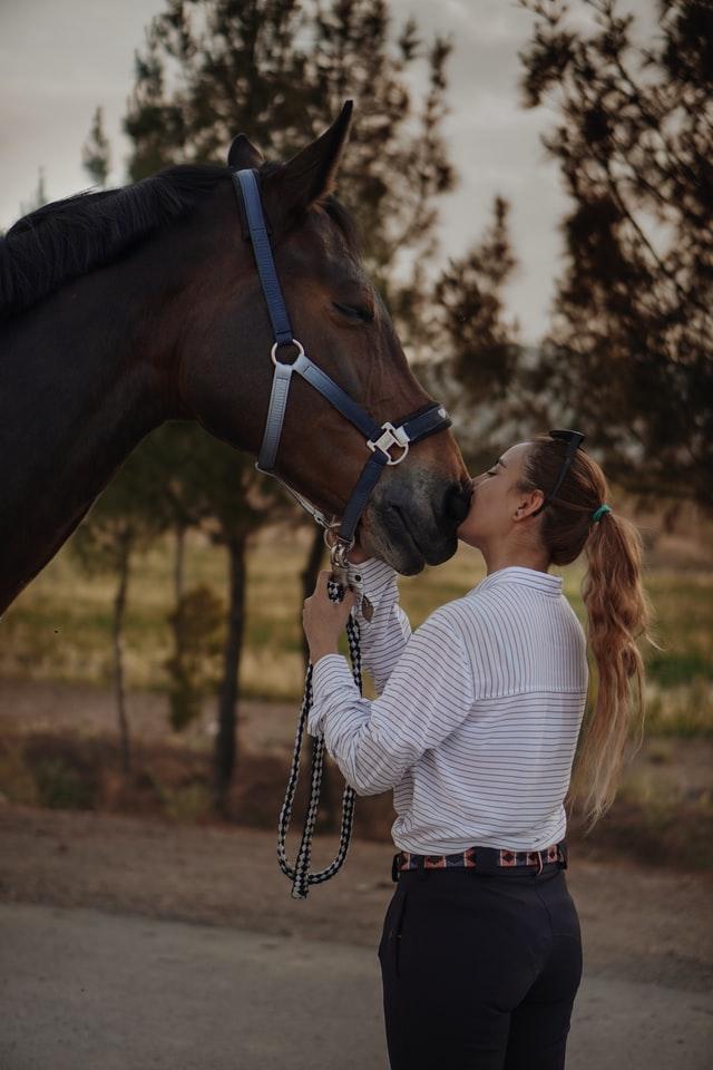 Une cavalière embrasse son cheval.